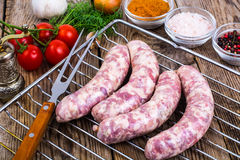 Homemade sausages in a natural shell with spices on grill. Studio Photo Stock Photo