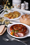 Homemade sausages and potato pancakes, whole grain bread on white plates, table with two glasses of drink. Ukrainian Royalty Free Stock Photos