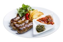 Homemade sausages with potatoes and sauce. On a white plate royalty free stock photography