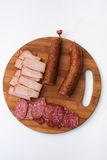Homemade sausages and smoked ham served on a kitchen wooden boar Stock Photography