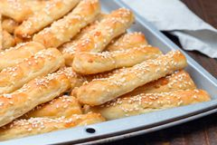 Homemade savory bread sticks with cheese and sesame on baking tray, horizontal royalty free stock photos