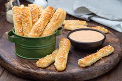 Homemade savory bread sticks with cheese and sesame in basket, served with sauce on wooden board, horizontal royalty free stock photos