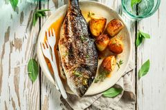 Homemade seabream and potatoes with cherry tomatoes and thyme. On old table royalty free stock photography