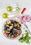 Homemade seafood Black pasta spaghetti with clams mussels octopus vongole in pan with white wine on marbled background stock photo
