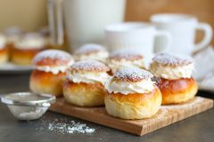 Homemade semla buns on the wooden desk. Homemade semla or vastlakukkel in Estonia is a traditional sweet roll with whipped cream made in Scandinavic and Baltic stock photo