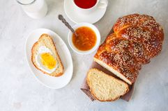 Homemade sesame seed Challah bread, a cup of tea, orange jam an royalty free stock photos