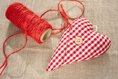 Homemade sewed red cotton love heart. Closeup. Royalty Free Stock Photos
