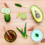 Homemade skin care and body scrub with natural ingredients avocado ,aloe vera ,cucumber and honey set up on wooden background. stock image