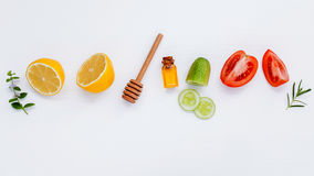 Homemade skin care and body scrubs with natural ingredients lemon,cucumber ,tomato slice,mint ,rosemary and honey set up on white. Wooden background with flat royalty free stock photography