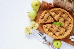 Homemade sliced apple pie on the wooden board decorated with fresh green apples, sugar cubes, mint leaves. Vegetarian tart stock photography