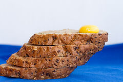 Homemade sliced bread with cereals and fresh egg on a blue background Royalty Free Stock Image