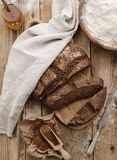 Homemade sliced round rye bread on a wooden table with malt and. Flour. Top view stock photos