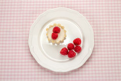 Homemade small cake with cream cheese and fresh garden raspberri. Es in white porcelain plate on a checkered napkin, top view Stock Photography