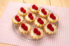 Homemade small cakes with cream cheese and fresh raspberries on. A cotton napkin with a checkered pattern, top view Stock Photos