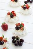 Homemade small pavlova meringue cakes with mascarpone cream, strawberries, cherries and fresh mint leaves Stock Images