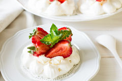 Homemade small strawberry pavlova meringue cakes with mascarpone cream and fresh mint leaves Stock Images