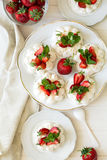 Homemade small strawberry pavlova meringue cakes with mascarpone cream and fresh mint leaves Stock Photo