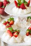Homemade small strawberry pavlova meringue cakes with mascarpone cream and fresh mint leaves Royalty Free Stock Photos