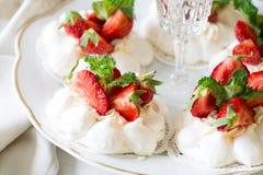 Homemade small strawberry pavlova meringue cakes with mascarpone cream and fresh mint leaves Stock Photos