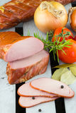 Homemade smoked Pork Loin. Digital smoker. Fresh and tender smoked pork meat. Tender Apple Smoked Pork Loin with tomatoes and onions on the wooden background stock image