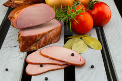 Homemade smoked Pork Loin. Digital smoker. Fresh and tender smoked pork meat. Tender Apple Smoked Pork Loin with tomatoes and onions on the wooden background stock photo