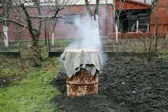 Homemade smokehouse in garden. Winter time. Smoke. Smoked sausages in traditional way Royalty Free Stock Image