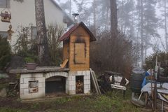 Homemade smokehouse in the morning mist. Domestic production of sausages. Smokehouse at the house in the woods. Traditional food royalty free stock photography