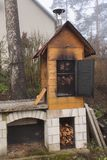 Homemade smokehouse in the morning mist. Domestic production of sausages. Smokehouse at the house in the woods. Traditional food royalty free stock photos