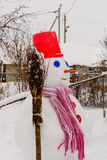 Homemade Snowman stands in winter landscape smiling at the camera. In the yard Stock Photo