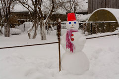 Homemade Snowman stands in winter landscape smiling at the camera. In the yard Royalty Free Stock Image