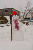 Homemade Snowman stands in winter landscape smiling at the camera. In the yard Royalty Free Stock Photo
