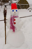 Homemade Snowman stands in winter landscape smiling at the camera. In the yard Royalty Free Stock Photos