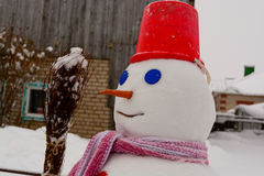 Homemade Snowman stands in winter landscape smiling at the camera. In the yard Stock Images