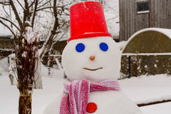 Homemade Snowman stands in winter landscape smiling at the camera. In the yard Royalty Free Stock Photography