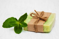 Homemade soap  with fresh mint leaves. On a old white wooden background Stock Photo