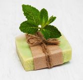 Homemade soap  with fresh mint leaves. On a old white wooden background Stock Images