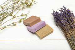Homemade soap pile with dried lavender bunch on wooden surface. Close-up view of homemade soap pile with dried lavender bunch on wooden surface stock images