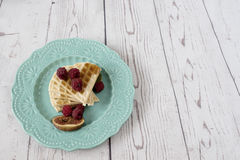 Homemade soft Belgian heart shaped waffles with raspberries and figs, covered with honey on turquoise blue plate. Royalty Free Stock Images
