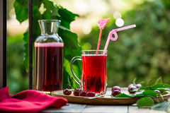 Homemade sour cherry compote in glass cup with jar on bamboo tray Royalty Free Stock Photos
