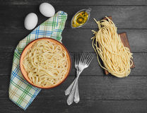Homemade spaghetti noodles. Cooked spaghetti noodles in a brown ceramic bowl. Uncooked spaghetti noodles on board. Ingredients for home-made noodles chicken eggs Royalty Free Stock Images