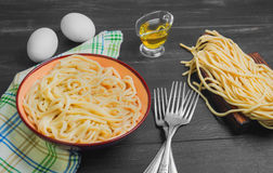 Homemade spaghetti noodles. Cooked spaghetti noodles in a brown ceramic bowl. Uncooked spaghetti noodles on board. Ingredients for home-made noodles chicken eggs Royalty Free Stock Image
