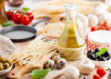 Homemade spaghetti pasta with quail eggs with botle of olive oil and cheese on wooden background. Classic italian village food. Ga royalty free stock photos