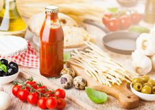 Homemade spaghetti pasta with quail eggs with bottle of tomato sauce and cheese on wooden background. Classic italian village food royalty free stock photo