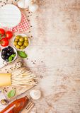 Homemade spaghetti pasta with quail eggs with bottle of tomato sauce and cheese on wooden background. Classic italian village food royalty free stock image