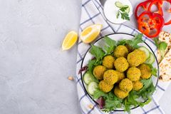 Homemade spicy chickpea falafel garnished with fresh vegetable and yogurt on a plate over light concrete background. Israeli cuisine concept stock image