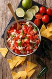 Homemade spicy pico de gallo close-up in a bowl and nachos. Vert. Homemade spicy pico de gallo close-up in a bowl and nachos on the table. Vertical top view from royalty free stock photos