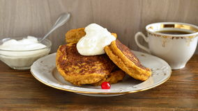 Homemade spicy pumpkin pancakes with honey and sour cream. Fritters Royalty Free Stock Image