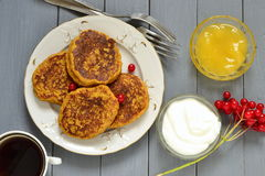 Homemade spicy pumpkin pancakes with honey and sour cream, fritters. Top view Stock Photography