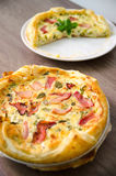 Homemade Spinach and Bacon Egg Quiche in a pie crust on wood board. French cuisine flat design Royalty Free Stock Photos