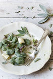 Homemade spinach dumplings with sage leafs, butter curls, flowers on plate with fork Royalty Free Stock Images